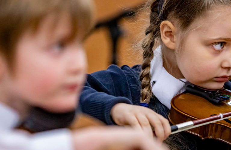 2 schoolchildren are in the music class, one of them is out of focus, the other is playing the viola in the class