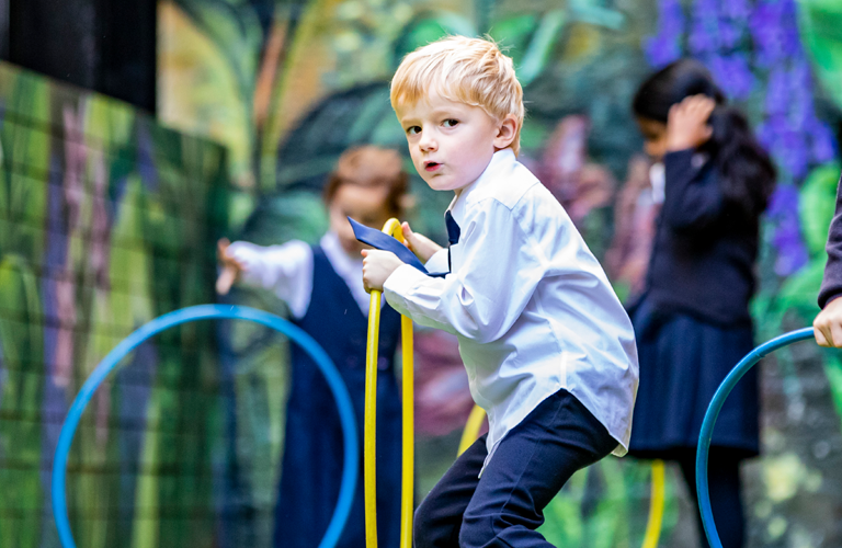 A young school boy is looking at the camera as he holds a yellow hula hoop