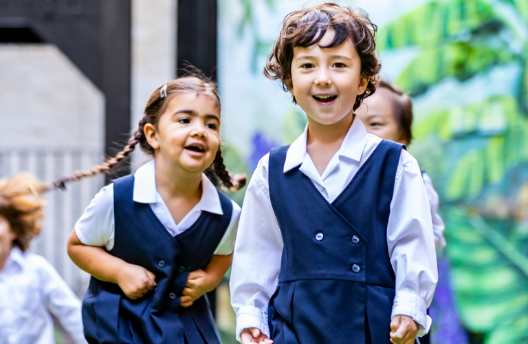 A group of children running across the school playground smiling